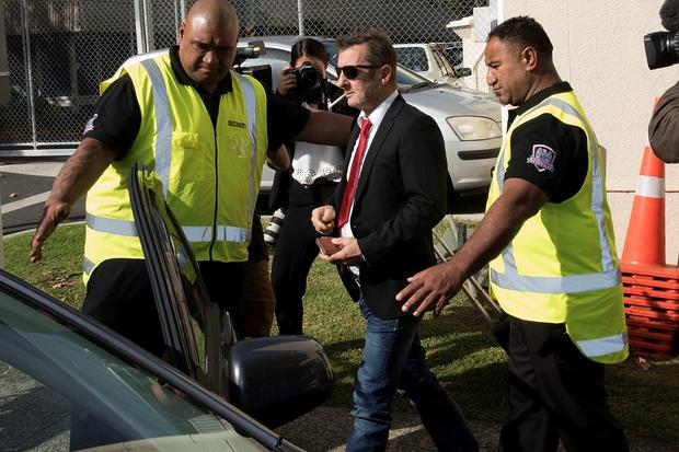 Former AC/DC drummer Phil Rudd leaves the District Court in Tauranga, New Zealand, flanked by security guards yesterday. Photo: Getty Images