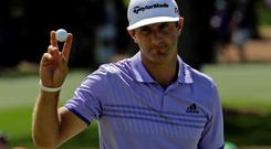 Dustin Johnson waves after a birdie on the second green during the third round of the Masters golf tournament