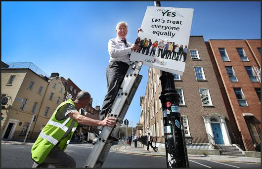 Minister Alex White hangs Labour's Vote Yes Campaign posters outside Dail Eireann. Photo: Steve Humphreys