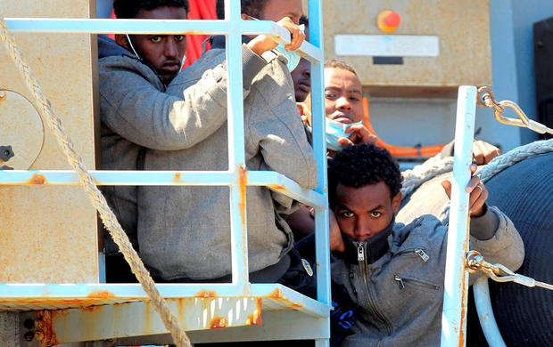Migrants stand on board Italian Navy ship Chimera before disembarking in the southern harbour of Salerno. Photo: Reuters