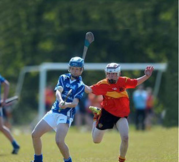Coláiste Eanna's Adam Kelleher strikes the sliotar as St Fintan's closes in during their Dublin Juvenile 'A' Hurling semi-final. Photo: Caroline Quinn