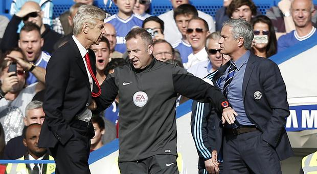 Chelsea's Jose Mourinho and Arsene Wenger of Arsenal are kept apart by the fourth official Jonathan Moss during the Premier League game at Stamford Bridge on October 5