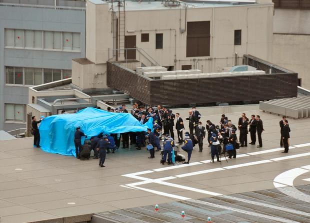 Investigators gather around a small drone covered with blue sheets on the roof of Prime Minister Shizo Abe's official residence in Tokyo. (Masakazu Mitsuyama/Kyodo News via AP) JAPAN OUT, MANDATORY CREDIT
