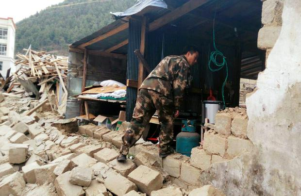 A rescuer looks at a damaged house, after a 7.9 magnitude earthquake hit Nepal, in Xigaze Prefecture, Tibet Autonomous Region, China. REUTERS/Stringer