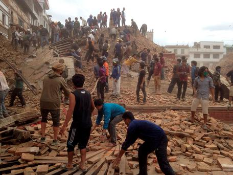 Volunteers help with rescue work at the site of a building that collapsed after an earthquake in Kathmandu, Nepal. AP Photo/ Niranjan Shrestha
