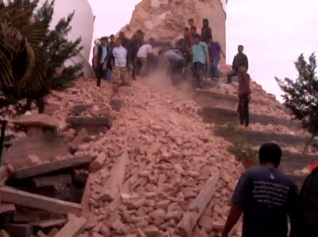 In this image from AP video people search in a buildings rubble in Kathmandu, Nepal after a strong earthquake hit the area, (AP video via AP)