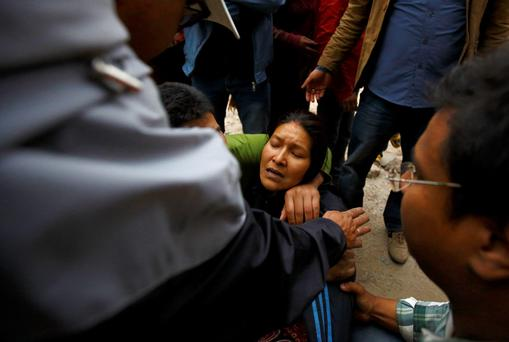 A woman cries as her son was trapped inside a collapsed house after an earthquake hit, in Kathmandu, Nepal April 25, 2015. The powerful earthquake struck Nepal and sent tremors through northern India on Saturday, killing hundreds of people, toppling an historic 19th-century tower in the capital Kathmandu and touching off a deadly avalanche on Mount Everest. REUTERS/Navesh Chitrakar