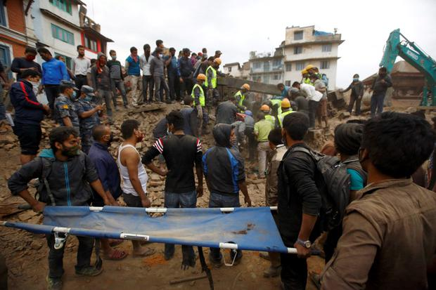 Rescue workers search for bodies as a stretcher is kept ready after an earthquake hit, in Kathmandu, Nepal April 25, 2015. The powerful earthquake struck Nepal and sent tremors through northern India on Saturday, killing hundreds of people, toppling an historic 19th-century tower in the capital Kathmandu and touching off a deadly avalanche on Mount Everest. REUTERS/Navesh Chitrakar