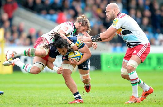 Sale Sharks' TJ Loane is tacked by Harlequins Luke Wallace (left) and George Robson (right), during the Aviva Premiership match at the AJ Bell Stadium
