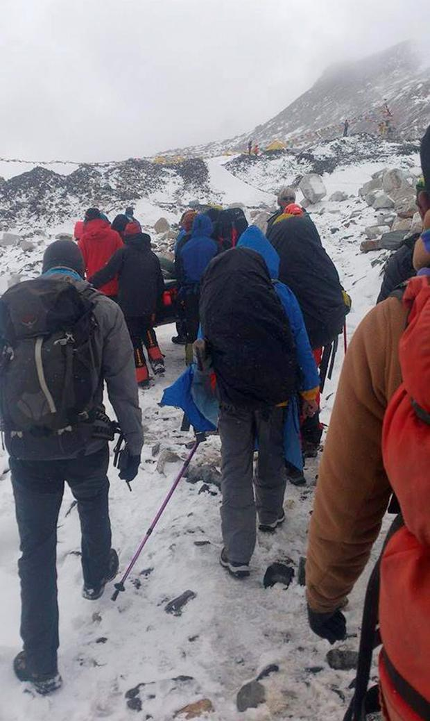 Climbers and guides carry an injured after an avalanche struck Everest Base Camp in Nepal, Saturday, April 25, 2015. An avalanche triggered by a massive earthquake in Nepal smashed into a base camp between the Khumbu Icefall, a notoriously treacherous rugged area of collapsed ice and snow, and the base camp where most climbing expeditions are, said Ang Tshering of the Nepal Mountaineering Association. (AP Photo/Pasang Dawa Sherpa)