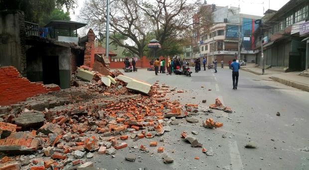 People gather in an intersection near a damaged building in Kathmandu, Nepal, Saturday, April 25, 2015. A strong magnitude-7.9 earthquake shook Nepal's capital and the densely populated Kathmandu Valley before noon Saturday, causing extensive damage with toppled walls and collapsed buildings, officials said. (AP Photo/Tashi Sherpa)