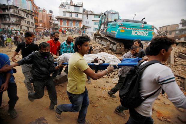 Volunteers carry the body of a victim on a stretcher, recovered from the debris of a building that collapsed after an earthquake in Kathmandu, Nepal, Saturday, April 25, 2015. A strong magnitude-7.9 earthquake shook Nepal's capital and the densely populated Kathmandu Valley before noon Saturday, causing extensive damage with toppled walls and collapsed buildings, officials said. (AP Photo/ Niranjan Shrestha)