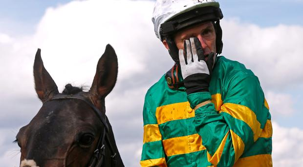 Tony McCoy wipes away a tear after finishing third on Box Office, his last ride at Sandown on Saturday