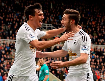 Jack Cork celebrates scoring Swansea's third goal with teammate Matt Grimes against Newcastle United at St James' Park yesterday