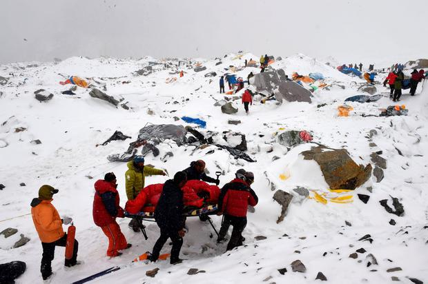Rescuers use a makeshift stretcher to carry an injured person after an avalanche triggered by an earthquake flattened parts of Everest Base Camp. AFP PHOTO/Roberto SCHMIDTROBERTO SCHMIDT/AFP/Getty Images