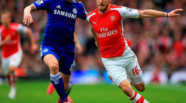 Cesc Fabregas battles it out with Aaron Ramsey