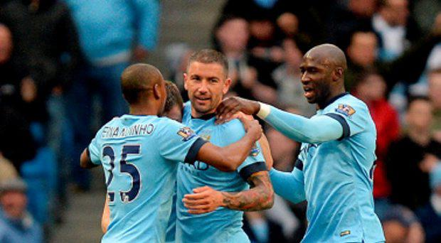 Manchester City's Aleksandar Kolarov (centre) celebrates scoring his side's second goal with Fernandinho (left) and Eliaquim Mangala during the Barclays Premier League match at the Etihad Stadium, Manchester.