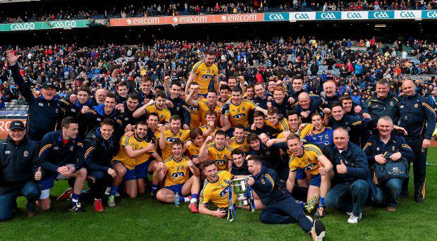 The Roscommon players and backroom staff celebrate with the cup