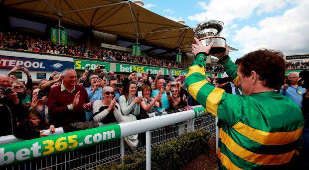 Tony McCoy parades the Champion Jockey Trophy during the bet365 Jump Finale at Sandown Racecourse