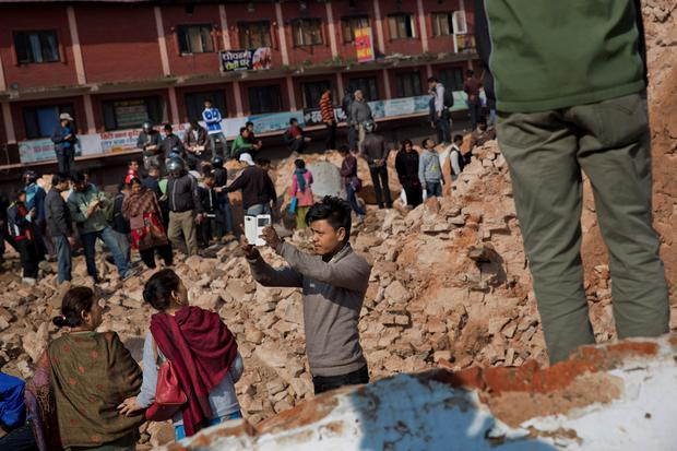 A man takes a selfie at the historic Dharahara Tower, a city landmark, that was damaged in Saturdays earthquake in Kathmandu, Nepal, Monday, April 27, 2015. (AP Photo/Bernat Armangue)