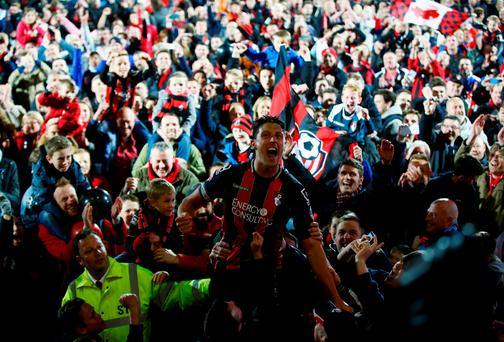 Captain Tommy Elphick of Bournemouth celebrates victory as fans invade the pitch after the Sky Bet Championship match between AFC Bournemouth and Bolton Wanderers at Goldsands Stadium
