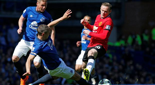 Manchester United's Wayne Rooney in action with Everton's Phil Jagielka and James McCarthy (Reuters / Andrew Yates)