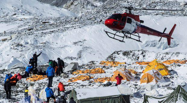 A rescue helicopter is shown at the Mount Everest south base camp in Nepal a day after a huge earthquake-caused avalanche killed at least 17 people, in this photo courtesy of 6summitschallenge.com