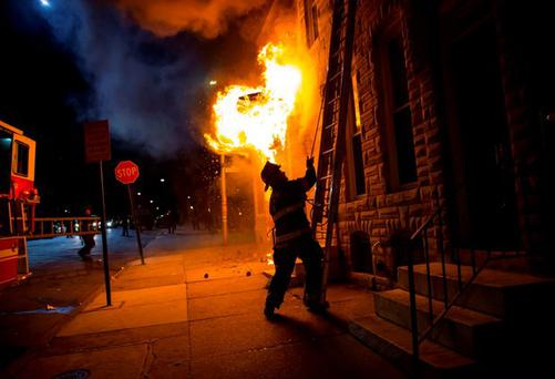 A Baltimore firefighter attacks a fire in a convenience store and residence during clashes after the funeral of Freddie Gray in Baltimore, Maryland. Reuters/Eric Thayer