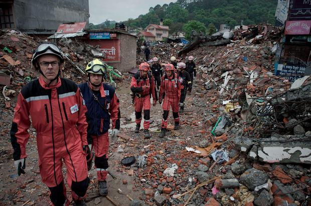 French rescue workers walk among earthquake debris as they look for survivors Credit: Nicolas Asfouri