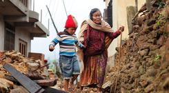 Jagot Kumari Rana, 79, is led through the rubble of collapsed homes by her grandson Sogat Rana, 7, in Paslang village near the epicenter of Saturday's massive earthquake in the Gorkha District of Nepal (AP Photo/Wally Santana)