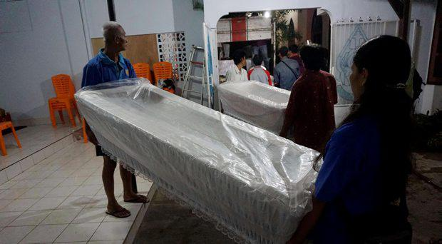 Workers load coffins from a church storage area ready to be taken to a police station in Cilacap, near the prison island of Nusakambangan, Central Java, Indonesia April 26, 2015 in this photo taken by Antara Foto