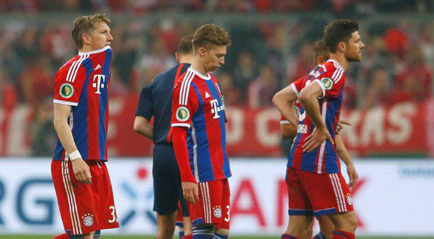 Bayern Munich players leave the pitch dejected after losing to Borussia Dortmund in the German Cup (DFB Pokal) semi-final soccer match in Munich, Germany April 28, 2015