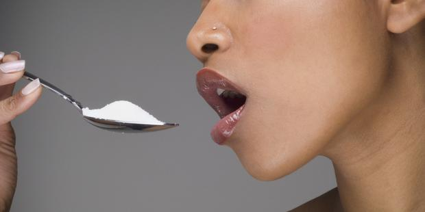 African woman eating spoon of sugar