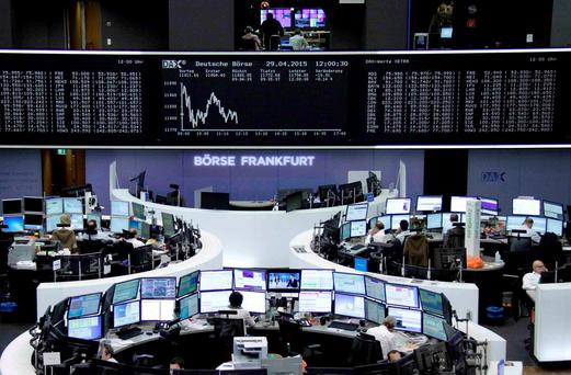 Traders are pictured at their desks in front of the DAX board at the Frankfurt stock exchange, Germany. Photo: Reuters
