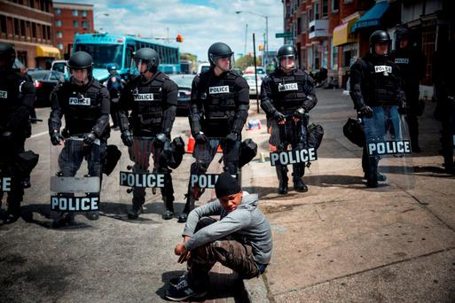 Daquan Green (17) sits on the curb while riot police stand guard near the pharmacy that was set on fire yesterday during rioting after the funeral of Freddie Gray. Photo: Getty Images