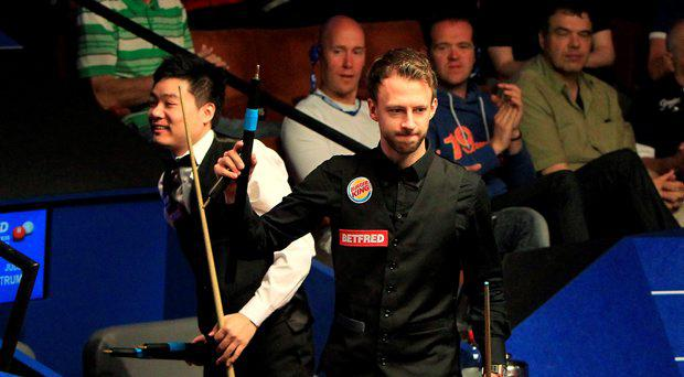 Judd Trump (right) celebrates beating Ding Junhui