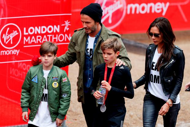 Romeo Beckham (C) receives the support of his family, brother Cruz Beckham (L), father David Beckham (2nd L) and mother Victoria Beckham after taking part in the junior marathon during the Virgin Money London Marathon on April 26, 2015 in London, England. (Photo by Steve Bardens/Getty Images)