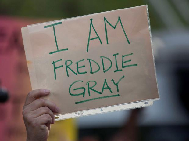 A protester carries a sign during a march trough Baltimore Credit: Andrew Caballero-Reynolds