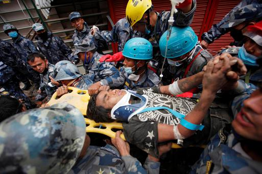 A teenage boy is rushed to hospital on a stretcher after being rescued alive from the debris of a building, five days after the earthquake in Kathmandu (AP Photo/Niranjan Shresta)