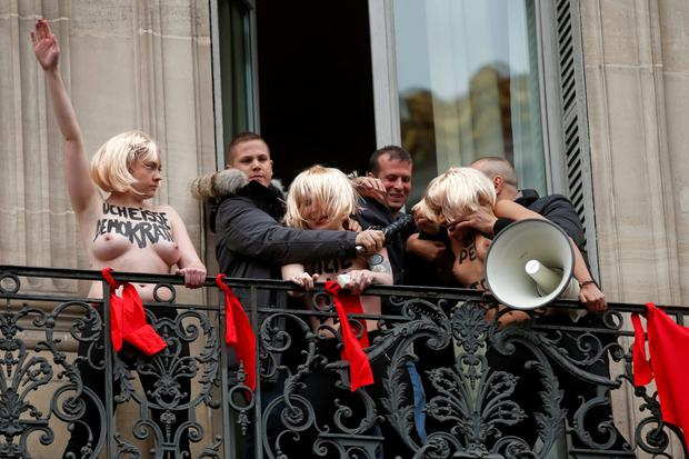 Security remove three topless activists from the Ukrainian feminist group Femen from a balcony as they give the Nazi salute to protest the gathering by France's far-right National Front political party leader Marine Le Pen REUTERS/Benoit Tessier