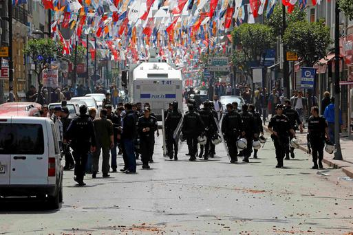 Policemen block a street to prevent people from gathering for May Day demonstrations near Taksim Square in Istanbu Credit: Umit Bektas