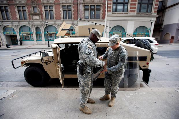 Two National Guardmen ready their equipment before a march for Freddie Gray Credit: Alex Brandon