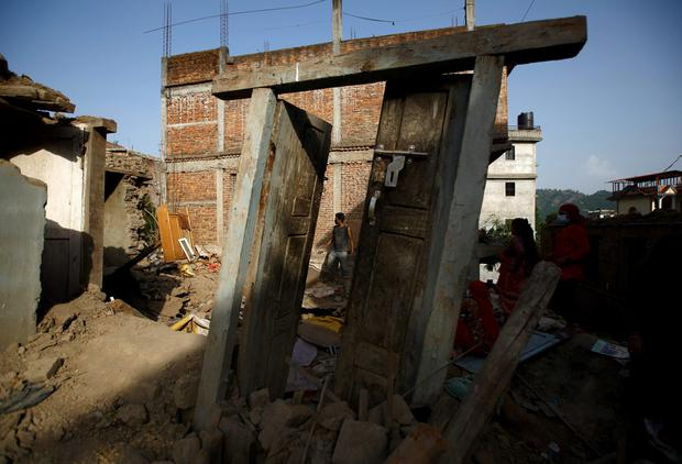 A man recovering goods from his house after it collapsed following Saturdays earthquake in Nepal Credit: Navesh Chitrakar