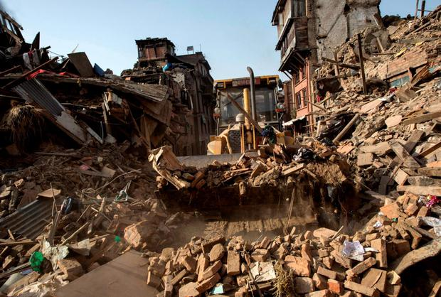 A bulldozer clears debris from collapsed houses in Bhaktapur, Nepal Credit: Danish Siddiqui