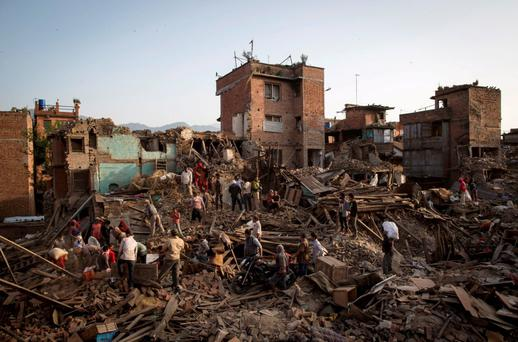 Residents clear debris as they look for their belongings in Nepal Credit: Danish Siddiqui
