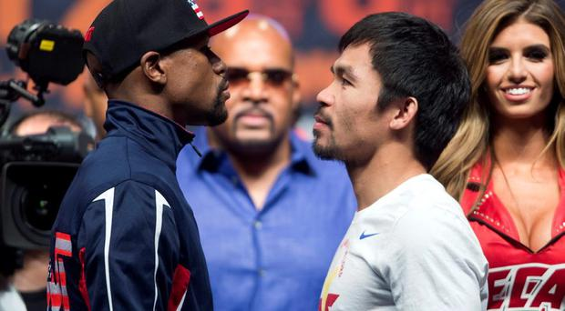 Undefeated WBC/WBA welterweight champion Floyd Mayweather Jr. (L) of the U.S. and WBO welterweight champion Manny Pacquiao of the Philippines face off during an official weigh-in at the MGM Grand Garden Arena in Las Vegas