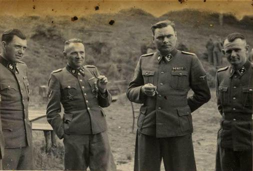 HORRIBLE HISTORIES: SS officers Dr. Josef Mengele, Rudolf Hoess, (former Commandant of Auschwitz), Josef Kramer (Commandant of Birkenau), and unidentified, at the SS retreat, Solahutte outside of Auschwitz, Poland in 1944. Last week Red Cross president Peter Maurer said the organisation 'lost its moral compass' during World War II