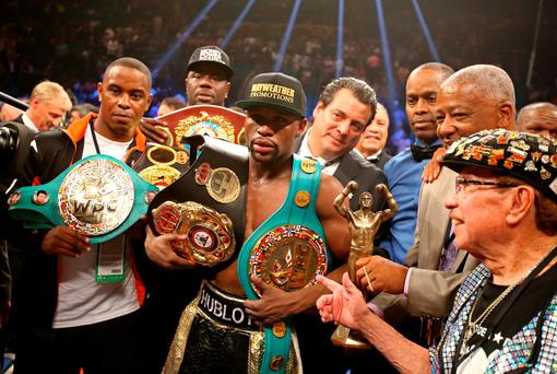 Floyd Mayweather Jr celebrates with the championship belts after defeating Manny Pacquiao