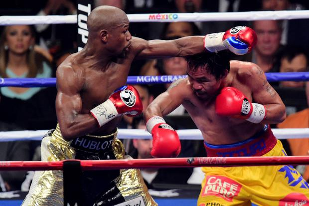 Floyd Mayweather (black/gold trunks) and Manny Pacquiao (yellow/red trunks) box during their world welterweight championship bout at MGM Grand Garden Arena. Mayweather won via unanimous decsion. Credit: Joe Camporeale-USA TODAY Sports