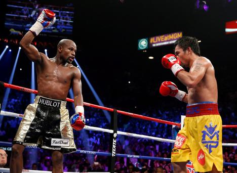 Floyd Mayweather Jr., left, celebrates during his welterweight title fight against Manny Pacquiao in May